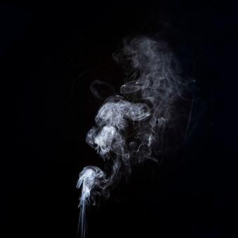 Движение белого дыма на черном фоне с копией пространства для написания текста