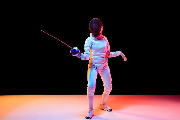 Movimento. teen girl in costume da scherma con la spada in mano isolati su sfondo nero, luce al neon. modello giovane che pratica e si allena in movimento, azione. copyspace. sport, gioventù, stile di vita sano.
