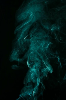 Movement of turquoise smoke spread on black background