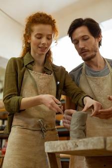 動きとテクニック。先生がプロセス全体を説明しながら粘土を切断しながらワイヤーツールを使用して楽しい晴れやかな生姜の女性
