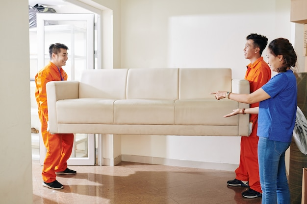Movers carrying sofa in house