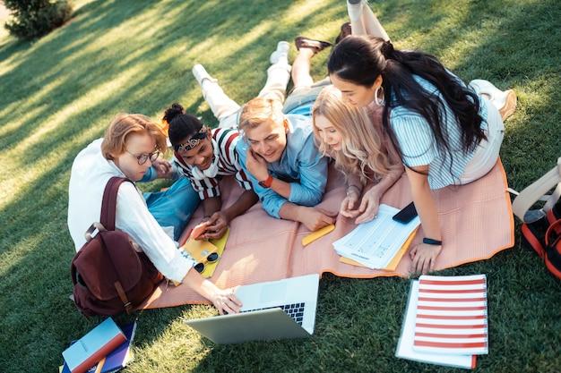 グループについての映画。フレンドリーな学生たちは、卒業式のために映画で自分自身を見て興奮しています。