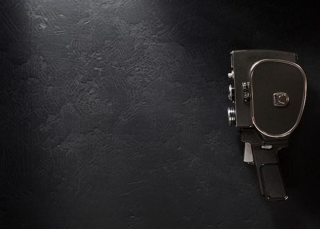 Movie camera at black background texture