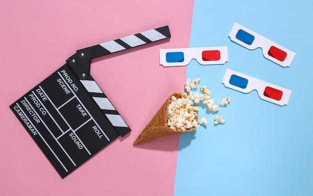 映画の下見板張り、ポップコーンとアイスクリームワッフルコーン、深い影とピンクと青の明るいパステルカラーの背景に3dメガネ、上面図。映画の時間。フラットレイ構成