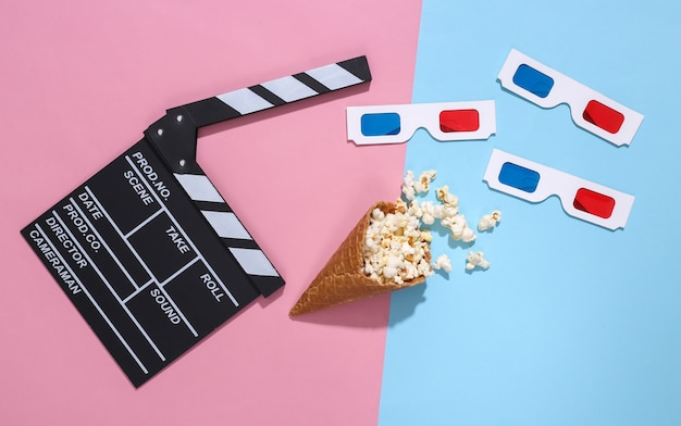 Movie clapboard, ice cream waffle cone with popcorn, 3d glasses on pink and blue bright pastel background with deep shadow, top view. movie time. flat lay composition