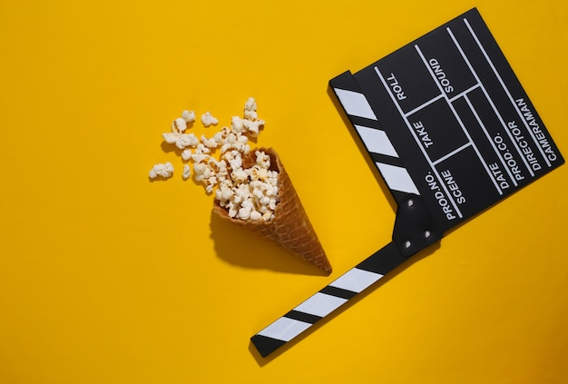 Movie clapboard, ice cream waffle cone with popcorn on yellow background with deep shadow, top view. movie time. flat lay composition