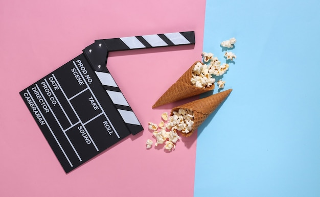 Movie clapboard, ice cream waffle cones with popcorn on pink and blue bright pastel background with deep shadow, top view. movie time. flat lay composition