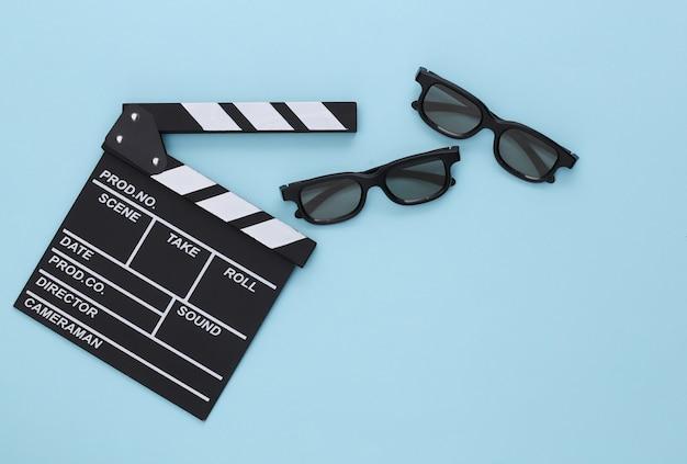 Клаппер кино и 3d-очки на синем. развлекательная индустрия. кино