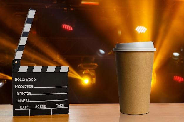 木の板の背景に映画のクラッパーとコーヒーのカップ Premium写真