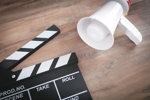 木製のテーブルの上の映画のクラッパーとメガホン。