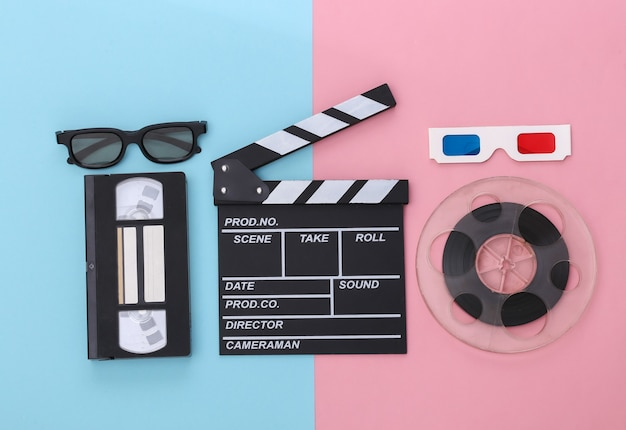 Movie clapper board and accessories on pink blue pastel background. retro 80s. cinema industry, entertainment. top view