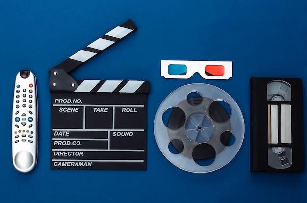 Доска с трещоткой кино и аксессуары на классическом синем фоне. ретро 80-х. киноиндустрия, развлечения. вид сверху