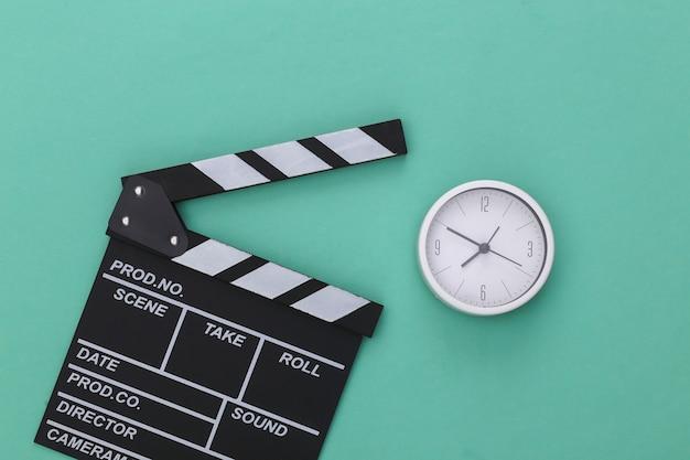 Доска трещотки кино и будильник на голубой пастельной предпосылке. кинопроизводство, кинопроизводство, индустрия развлечений. вид сверху