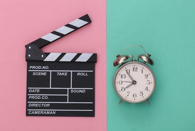 Доска с хлопушкой фильма и будильник на сине-розовом пастельном фоне. кинопроизводство, кинопроизводство, индустрия развлечений. вид сверху