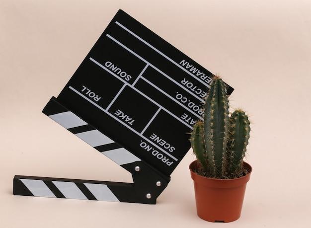 Доска трещотки кино и кактус на бежевом фоне. киноиндустрия, развлечения