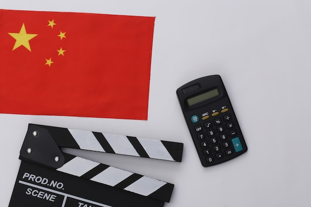 Доска трещотки кино и калькулятор, флаг китая на белой предпосылке. плата за кино. кинопроизводство, кинопроизводство. вид сверху