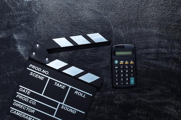 Доска с трещоткой кино и калькулятор на доске мела. киноиндустрия, развлечения