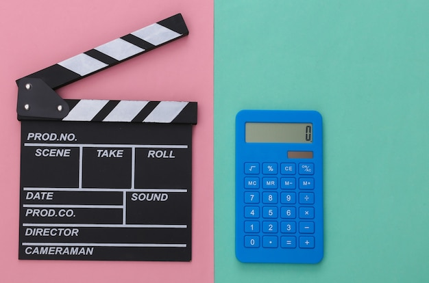Доска с трещоткой кино и калькулятор на розовом синем фоне. плата за кино. кинопроизводство, кинопроизводство. вид сверху