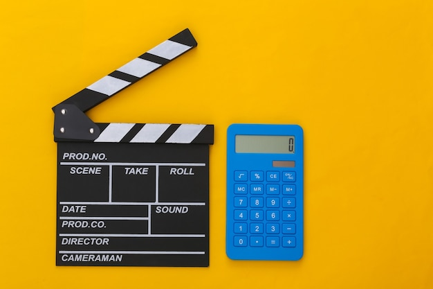 Доска с трещоткой кино и калькулятор на желтом фоне. плата за кино. кинопроизводство, кинопроизводство. вид сверху