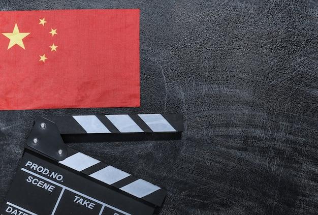 Доска с хлопушкой фильма и флаг китая на доске мелом. киноиндустрия, развлечения