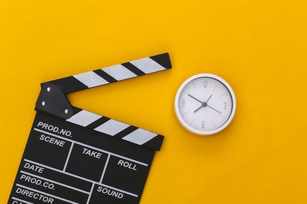 Доска трещотки кино и часы на желтом фоне. кинопроизводство, кинопроизводство, индустрия развлечений. вид сверху