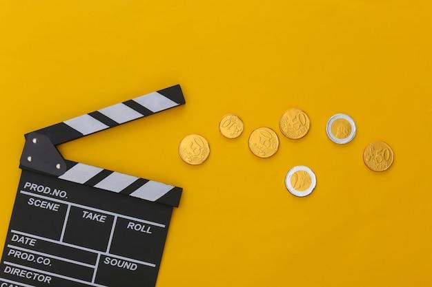 Доска трещотки кино и монеты на желтом фоне. плата за кино. кинопроизводство, кинопроизводство. вид сверху