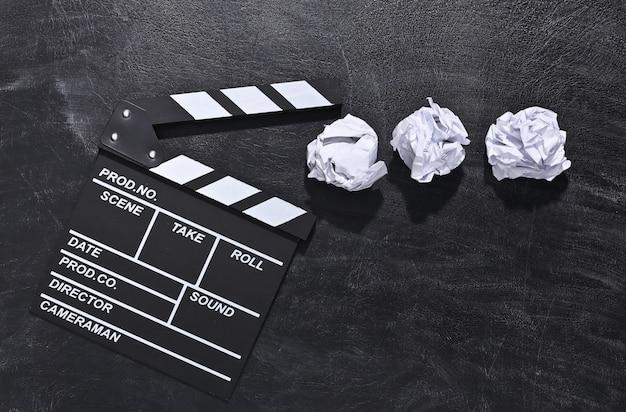 Доска с хлопушкой кино и скомканные бумажные шарики на доске мела. киноиндустрия, развлечения