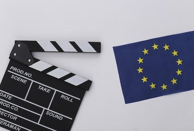 Доска трещотки кино и флаг ес на белой предпосылке. кинопроизводство, кинопроизводство, индустрия развлечений. вид сверху
