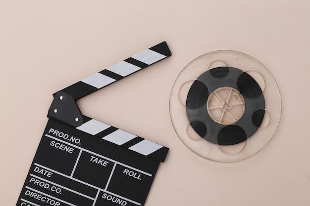 Доска с хлопушкой фильма и катушка пленки на бежевом фоне. киноиндустрия, развлечения. вид сверху