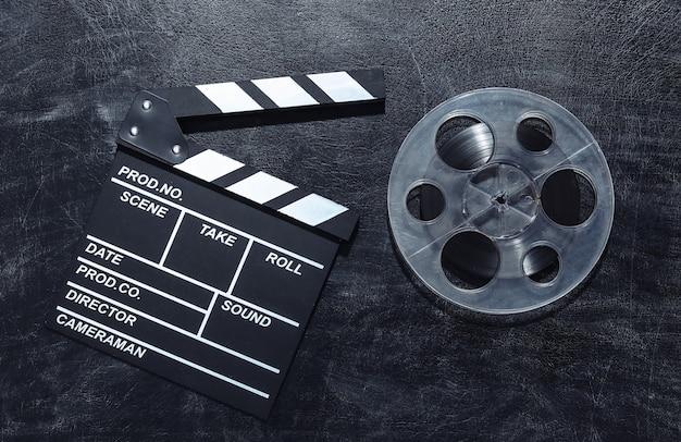 Доска с хлопушкой фильма и катушка пленки на доске мела. киноиндустрия, развлечения
