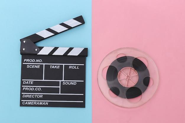 Доска с хлопушкой фильма и катушка пленки на розово-голубом пастельном фоне. киноиндустрия, развлечения. вид сверху