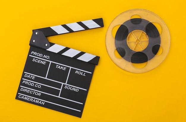 Доска с хлопушкой фильма и катушка пленки на желтом фоне. киноиндустрия, развлечения. вид сверху