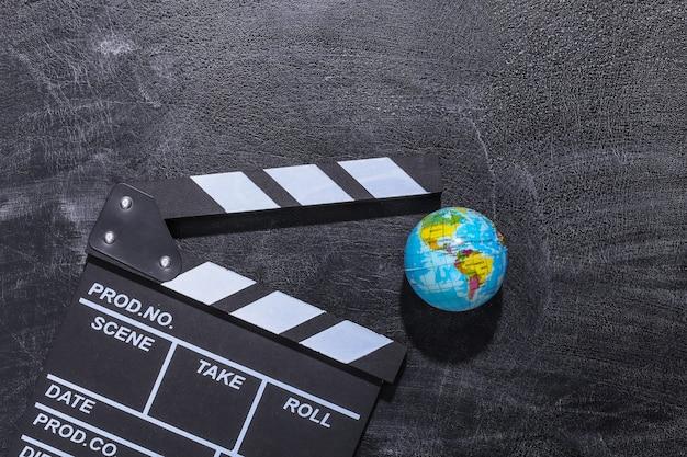 Доска с хлопушкой кино и глобус на доске мела. киноиндустрия, развлечения