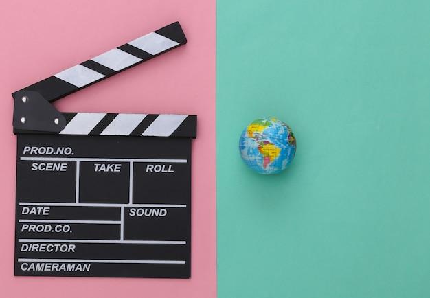 Доска трещотки кино и глобус на розовом синем фоне. кинопроизводство, кинопроизводство, индустрия развлечений. вид сверху