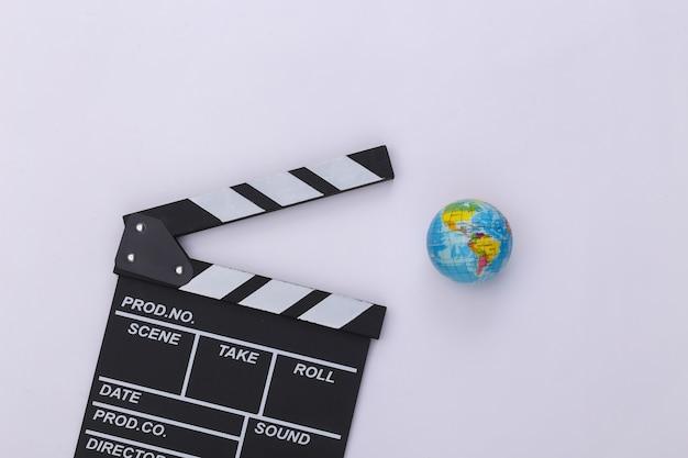 Доска трещотки кино и глобус на белой предпосылке. кинопроизводство, кинопроизводство, индустрия развлечений. вид сверху