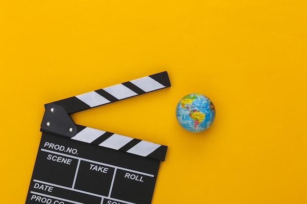 Доска трещотки кино и глобус на желтой предпосылке. кинопроизводство, кинопроизводство, индустрия развлечений. вид сверху
