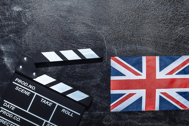Доска с хлопушкой кино и флаг великобритании на доске мелом. киноиндустрия, развлечения