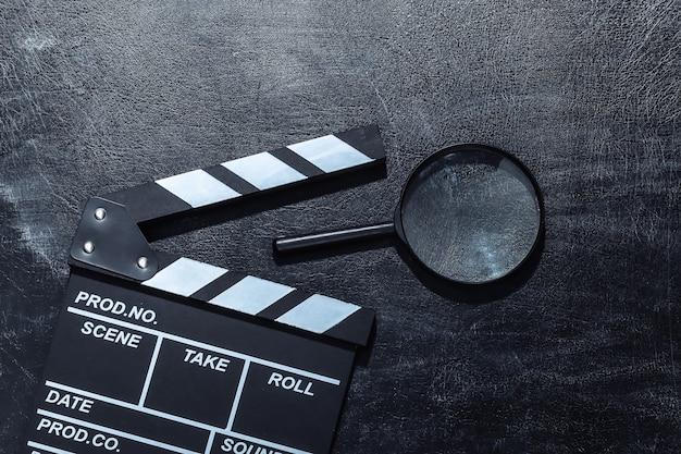 Доска с хлопушкой фильма и увеличительное стекло на доске мела. киноиндустрия, развлечения