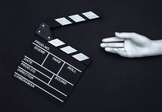 Доска с хлопушкой фильма и рука манекена на черном фоне