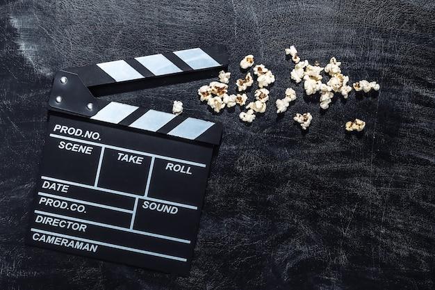映画のカチンコとチョーク黒板のポップコーン。映画産業、エンターテインメント