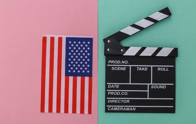 Доска с хлопушкой фильма и флаг сша на сине-розовом пастельном фоне. кинопроизводство, кинопроизводство, индустрия развлечений. вид сверху