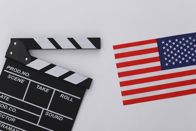 Доска трещотки кино и флаг сша на белой предпосылке. кинопроизводство, кинопроизводство, индустрия развлечений. вид сверху