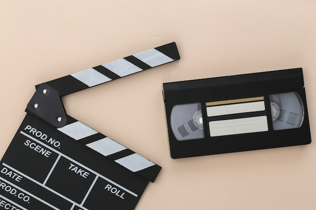 Доска с хлопушкой фильма и видеокассета на бежевом фоне. киноиндустрия, развлечения. вид сверху