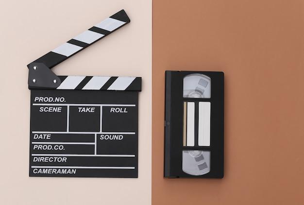 Доска с хлопушкой фильма и видеокассета на бежевом коричневом фоне. кинопроизводство, кинопроизводство, индустрия развлечений. вид сверху