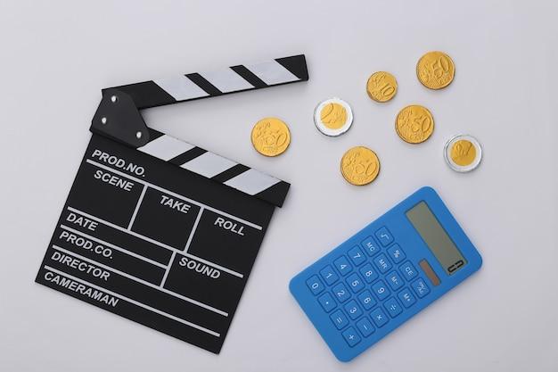 Доска трещотки кино, калькулятор и монеты на белой предпосылке. плата за кино. кинопроизводство, кинопроизводство. вид сверху