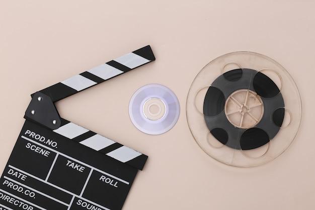 Доска с хлопушкой фильма, компакт-диск и катушка пленки на бежевом фоне. киноиндустрия, развлечения. вид сверху