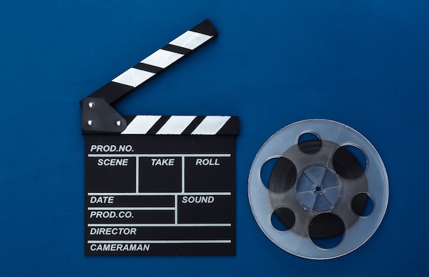 Movie clapper board and film reel on classic blue background. cinema industry, entertainment. top view