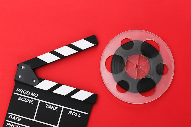 Movie clapper board and film reel on red background. cinema industry, entertainment. top view