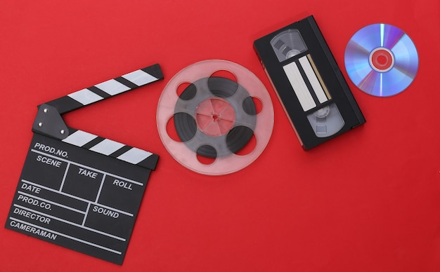 Movie clapper board and film reel, video cassette on red background. cinema industry, entertainment. top view