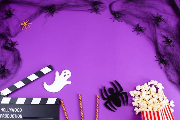 보라색 라일락 배경에 거미줄 거미 유령 눈의 영화 클래퍼 보드